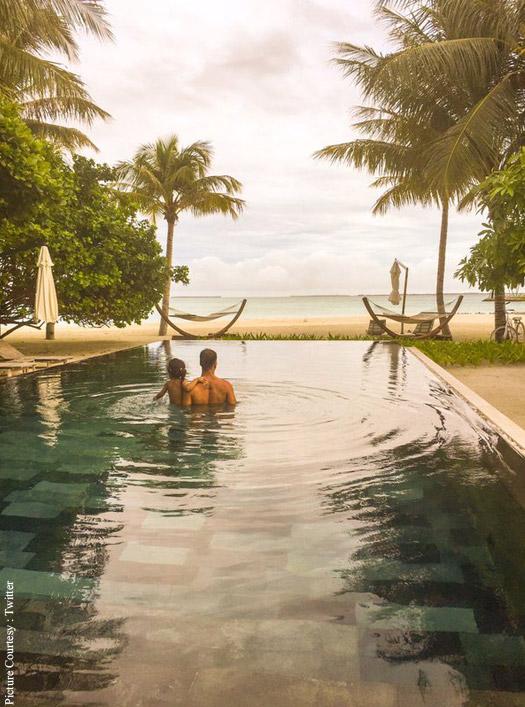 Alkshay Kumar and Nitara standing inside a pool looking at the beach